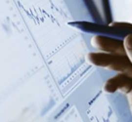 fotografía de un ordenador con unas gráficas en la pantalla y la mano de un científico pulsando la pantalla del ordenador con un boligrafo en uno de los procesos científicos