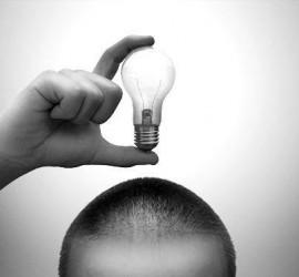 Fotografía en blanco y negro de la parte superior de una cabeza de un hombre que sujeta una bombilla simulando la innovación para el concurso de universitarios de la UGR