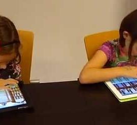 Fotografía de dos niñas pequeñas usando mediante dispositivos tablet la aplicación del videojuego ATO desarrollado por los informáticos de la Universidad de Granada