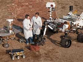 Un investigador junto a otro y el robot Curiosity